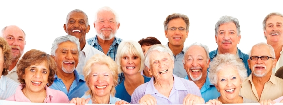 Group of happy retired people behind an empty billboard on white